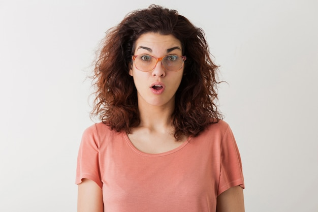 Young pretty stylish woman in glasses, curly hair, shocked, surprised face expression, funny emotion, isolated, pink t-shirt