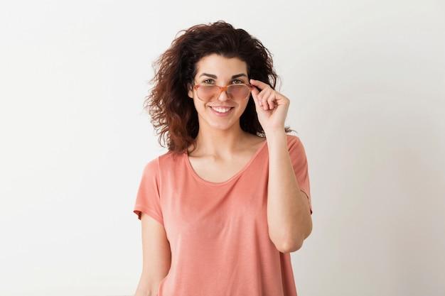 Молодая красивая стильная женщина, держащая очки, вьющиеся волосы, улыбка, положительные эмоции, счастливая, изолированная, розовая футболка