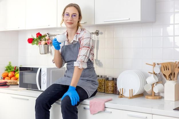 Молодая довольно стильная женщина, держащая белую кружку на белой кухне после сжатия, расслабляющая молодая женщина