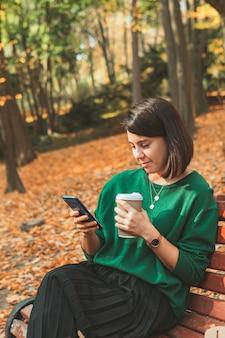 電話でコーヒーサーフィンインターネットを飲んで秋の公園に座っている若いかなりスタイリッシュな女性。コピースペース