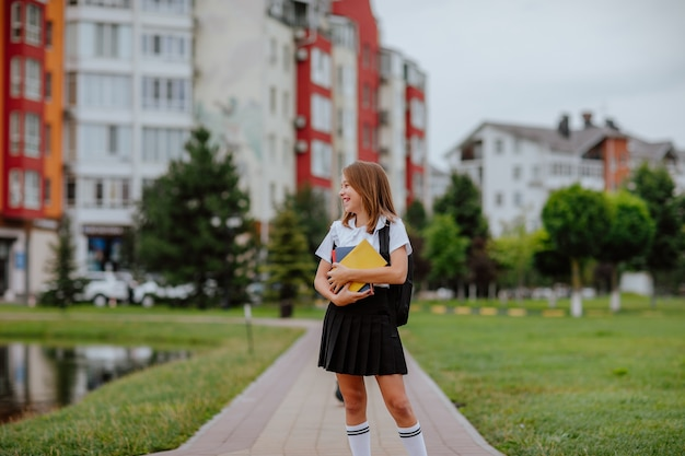 Young pretty teen girl in black and white school uniform holding books and posing in the city. back to school