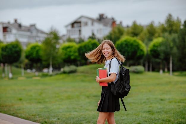 책을 들고 도시에서 포즈를 취하는 흑백 교복을 입은 젊은 예쁜 십대 소녀. 학교로 돌아가다