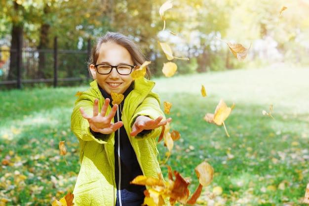 秋の庭で眼鏡をかけた若いかわいい十代の少女が歩き、喜びます。