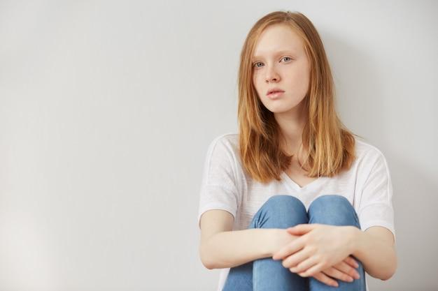 一人で悲しい絶望を家の床に座っている若いかなり10代の少女