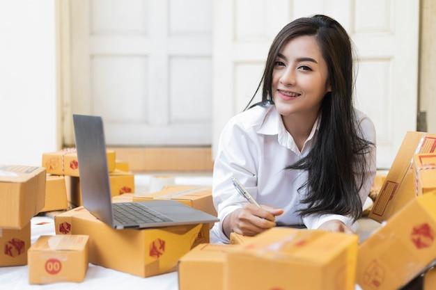 自宅で若いかなり10代の仕事は、宅配ボックスにメモを書きます。顧客、オンラインショッピングsme起業家、またはフリーランスの仕事の概念からの新規注文後に幸せなアジアの女性。