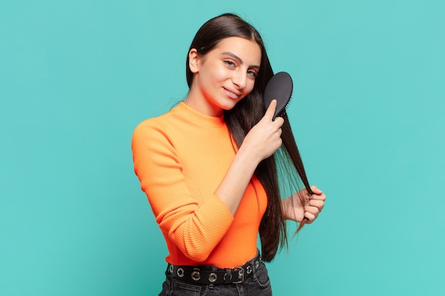 Young pretty teenager girl. happy and surprised expression. hair brush concept