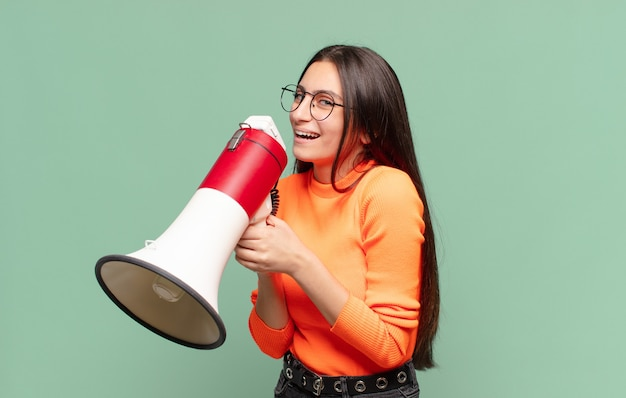 Young pretty teenager girl. happy and surprised expression. megaphone concept