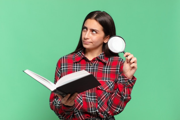 Young pretty teenager girl. searching in a book concept