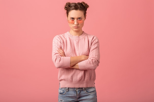 Young pretty thinking woman having a problem, looking down in pink sweater and sunglasses isolated on pink studio background