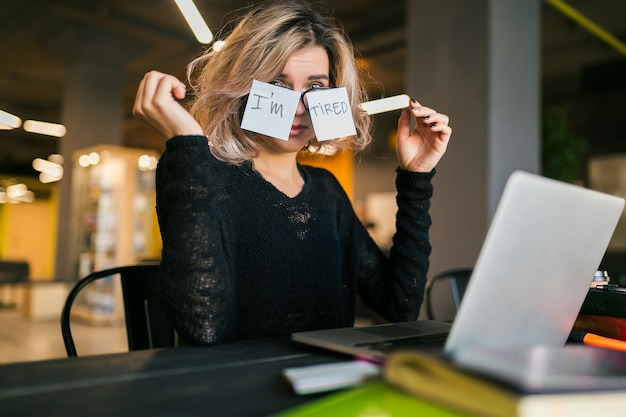 Young pretty tired woman with paper stickers on glasses sitting at table in black shirt working on laptop in co-working office, funny face emotion, problem, workplace, holding hands up
