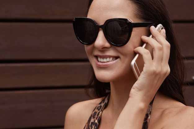 Young pretty tourist talking on mobile, wearing sunglasses and swimming suit with leopard print, smiling and looks happy