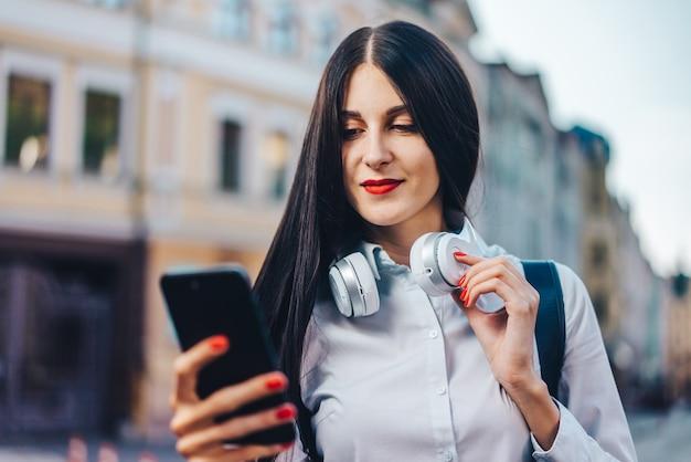 旧市街の通りに立って、携帯電話を使用して市内地図を閲覧しているバックパックを持つ若いきれいな観光客の女性