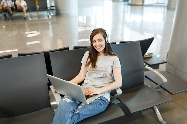 Молодая красивая туристическая женщина путешественника с наушниками, слушающая музыку, работает на ноутбуке, ждет в холле вестибюля в международном аэропорту
