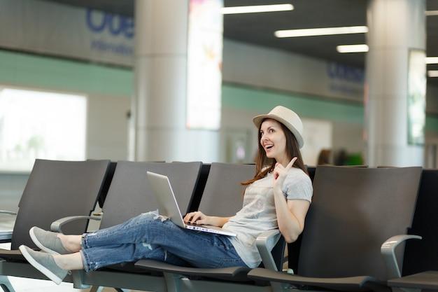 Giovane bella donna turistica viaggiatrice che lavora al computer portatile tenendo il dito alzato avendo un'idea in attesa nella hall dell'aeroporto internazionale