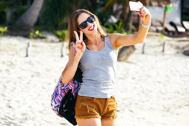 Donna giovane e carina viaggiatrice che fa foto sulla spiaggia assolata, viaggia da sola con lo zaino nel caldo paese tropicale, abbigliamento casual, corpo fitness, atmosfera avventurosa.