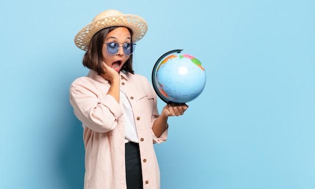 Молодая красивая женщина путешественника с картой земного шара мира