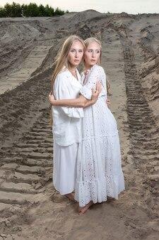 Молодые красивые близнецы с длинными светлыми волосами держатся за руки в песчаном карьере в элегантном белом платье, юбке, куртке