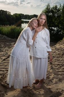 우아한 흰색 드레스에 모래 해변에서 포즈를 취하는 긴 금발 머리를 가진 젊은 예쁜 쌍둥이