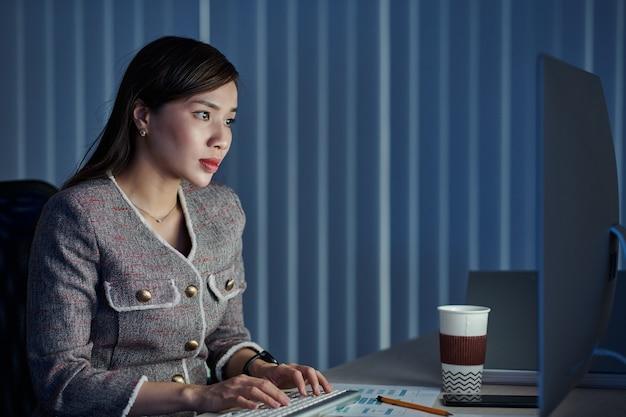 Молодая симпатичная вьетнамская бизнесвумен пьет кофе на вынос, работая в офисе весь день и завершает большой проект в срок