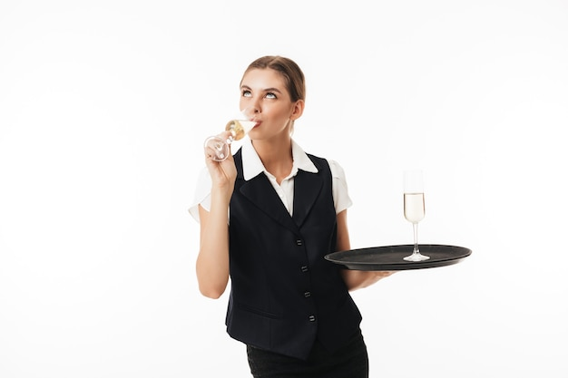 Young pretty waitress in uniform holding tray with glass dreamily