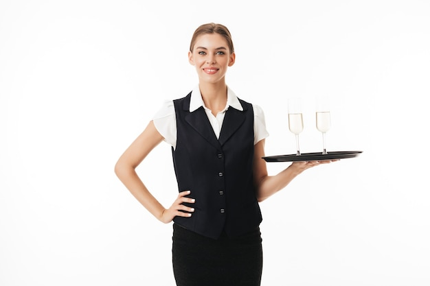 Young pretty waitress in uniform holding tray with glasses while dreamily