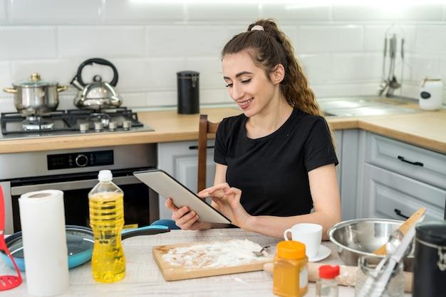 Молодая красивая жена готовит печенье дома с помощью цифрового планшета