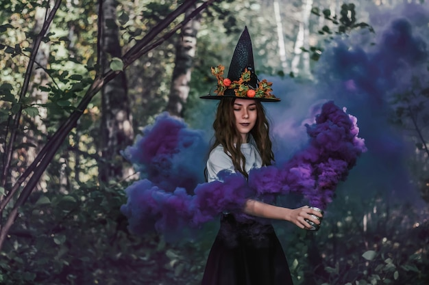 Young pretty witch in black hat and with purple fog in her hand close up in the forest.