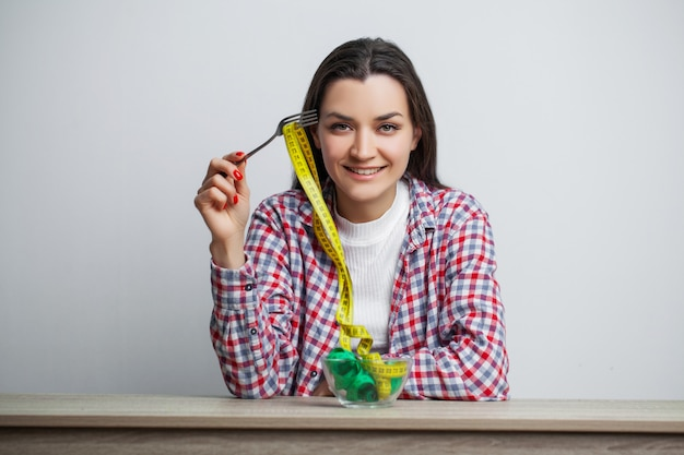 Young pretty woman adheres to diet with measuring tape on white wall