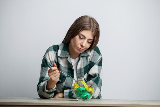 Молодая милая женщина придерживается диеты с измерительной ленты на белой стене