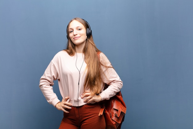 Young pretty woman against blue wall with a copy space