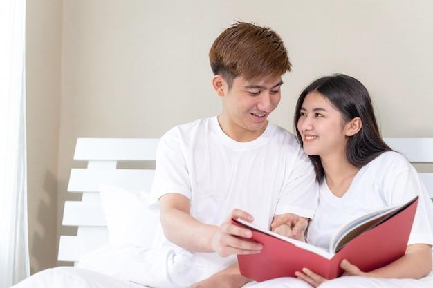 若いきれいな女性とハンサムなボーイフレンドは自宅のベッドで本を読んで