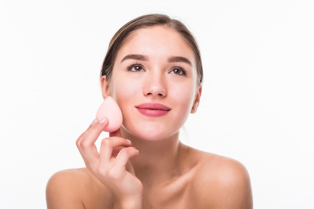 Young pretty woman applying blusher on her face with powder puff isolated on white wall