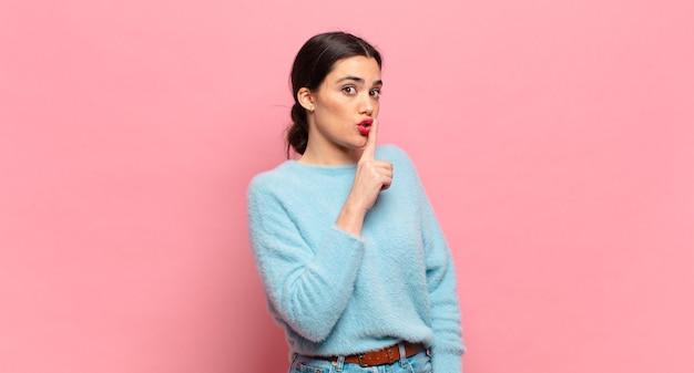 沈黙と静けさを求め、口の前で指をジェスチャーし、シャッと言うか、秘密を守る若いきれいな女性