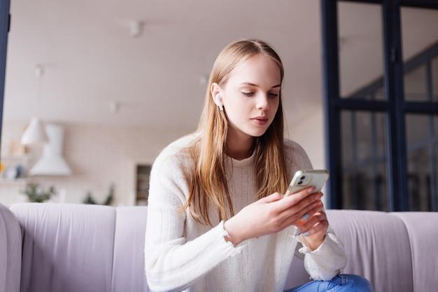 テキスト メッセージを入力する携帯電話でソファの上の若いきれいな女性