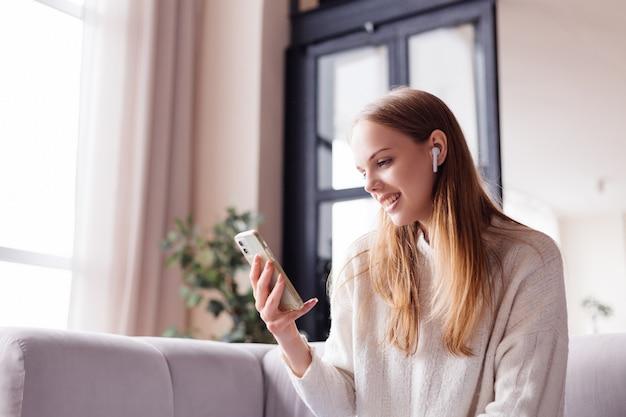自宅で携帯電話が付いているソファーの若いきれいな女性