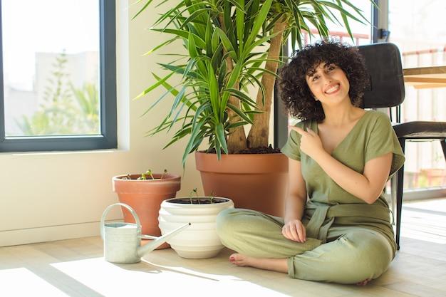 じょうろと植物を持つ自宅で若いきれいな女性