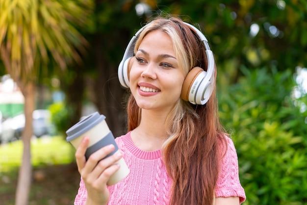 Молодая красивая женщина на открытом воздухе, слушая музыку и держа кофе на вынос