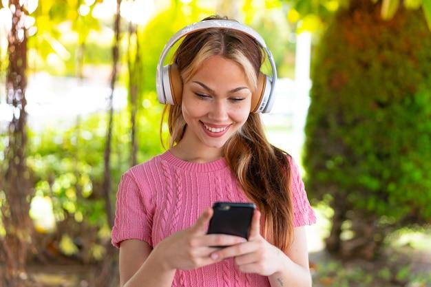 Молодая красивая женщина на открытом воздухе, слушая музыку и глядя на мобильный