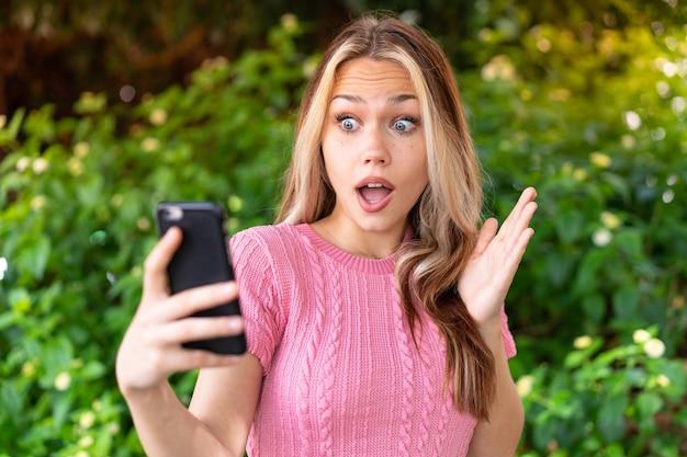 Молодая красивая женщина на открытом воздухе, глядя в камеру, используя мобильный телефон с удивленным выражением лица