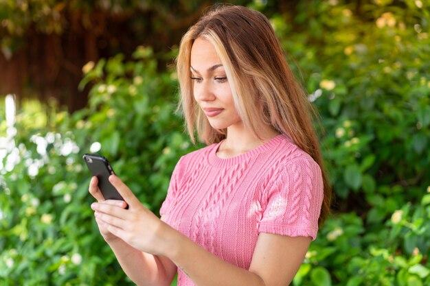 Молодая красивая женщина на открытом воздухе, отправив сообщение или электронное письмо с мобильного телефона