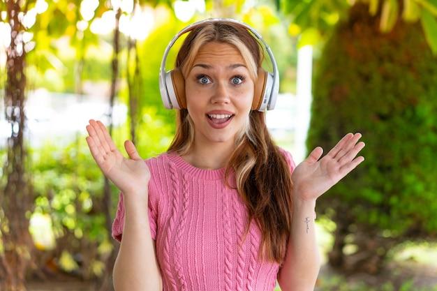Молодая красивая женщина на открытом воздухе удивлена и слушает музыку
