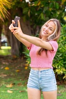 Молодая красивая женщина на открытом воздухе с помощью мобильного телефона и делает селфи