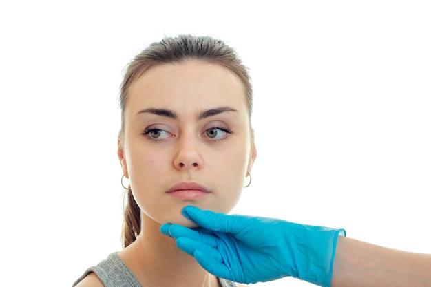 Молодая красивая женщина у пластического хирурга, изолированного на белой стене