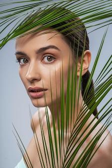이국적인 녹색 식물 뒤에 젊은 예쁜 여자