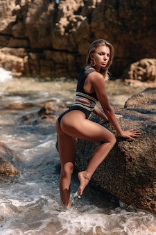Young pretty woman in black bikini posing on the rocky beach