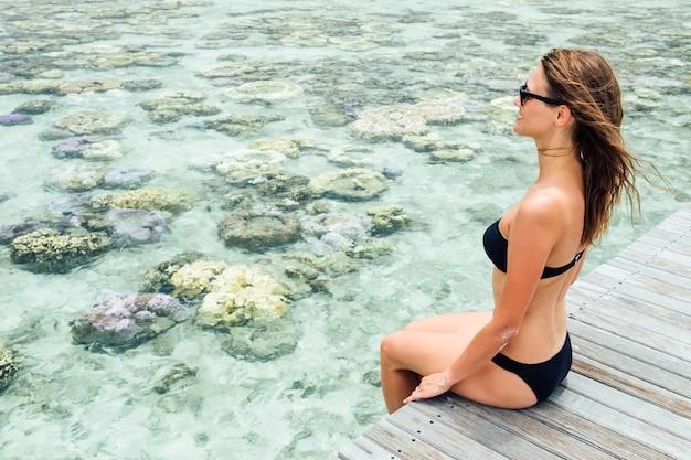 Young pretty woman in black bikini sitting alone on the pier near the sea