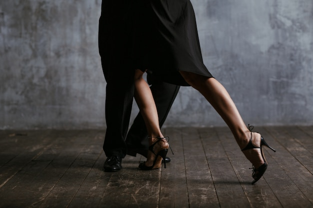 Young pretty woman in black dress and man dance tango. legs close up.