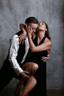 Young pretty woman in black dress and man dance tango