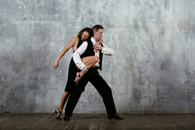 Young pretty woman in black dress and man dancing tango