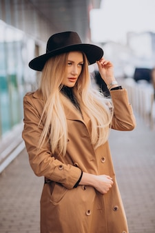 Young pretty woman in black hat and beige coat walking by mall